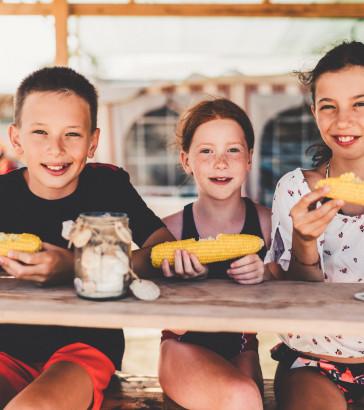 Kids eating sweet corn