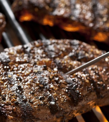 steak on a grill with meat thermometer