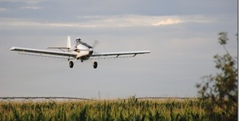 crop dusting plane over a field