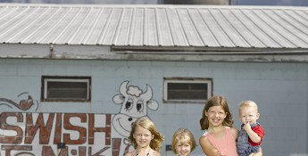 kids in front of milk sign
