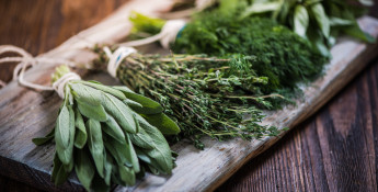 fresh herbs for cooking on wooden cutting board
