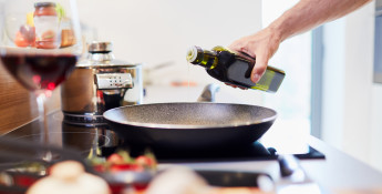Man Pouring Oil in Hot Pan