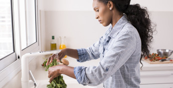 woman washing fresh herbs