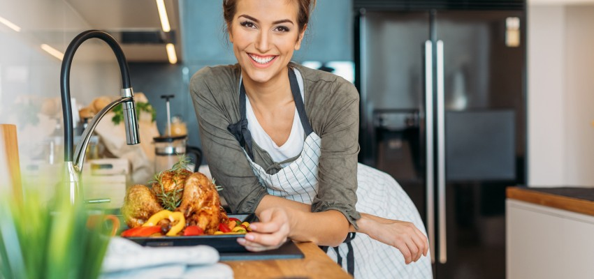 woman with cooked chicken in the kitchen