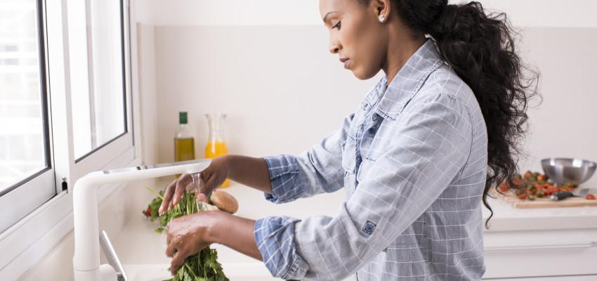 woman washing fresh herbs