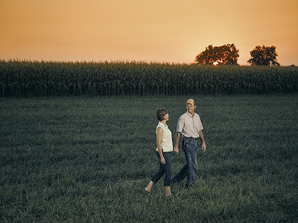 man and woman walking in front of corn field
