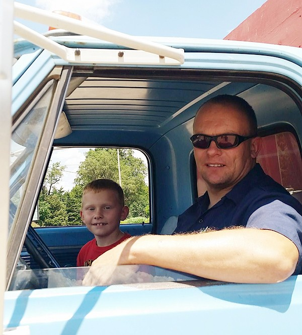 father and son in wheat truck