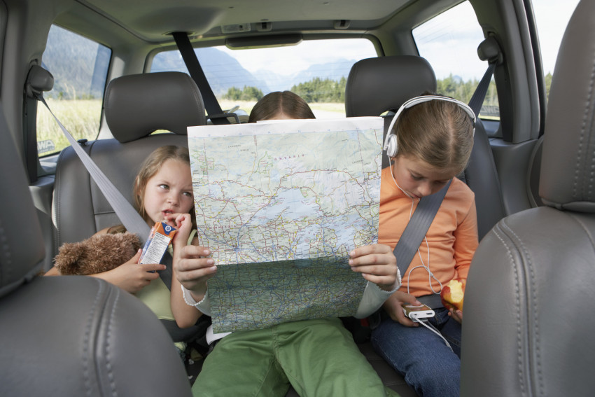 Kids on road trip looking at map