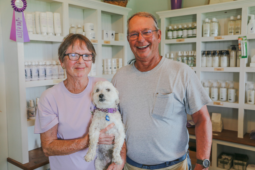 Dianne and Mike stand in their on-farm lavender shop with their dog, Augie.