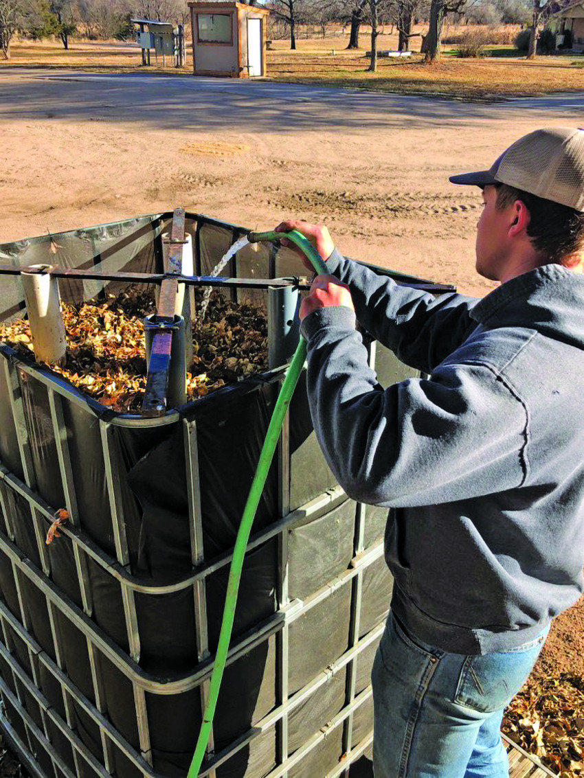 Connor Peirce adds water daily to his bioreactor compost system to keep it moist and microorganisms active. The four white pipes allow air to circulate through the reactor of leaves, straw, alfalfa and soil and provide a perfect habitat for microorganisms