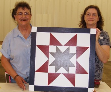 women with completed barn quilt