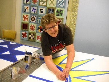 woman painting barn quilt