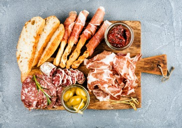 charcuterie board with meats, breads, spreads