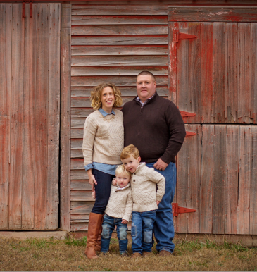 Katie Sawyer and family in front of red barn