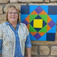woman standing next to barn quilt