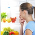 woman looking at fruits and veggies in refrigerator