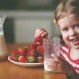 young girl eating strawberries and drinking milk