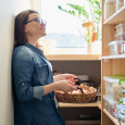 woman at home looking at pantry items with basket